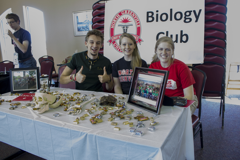 NGU biology majors give a thumbs up in regards to their booth.