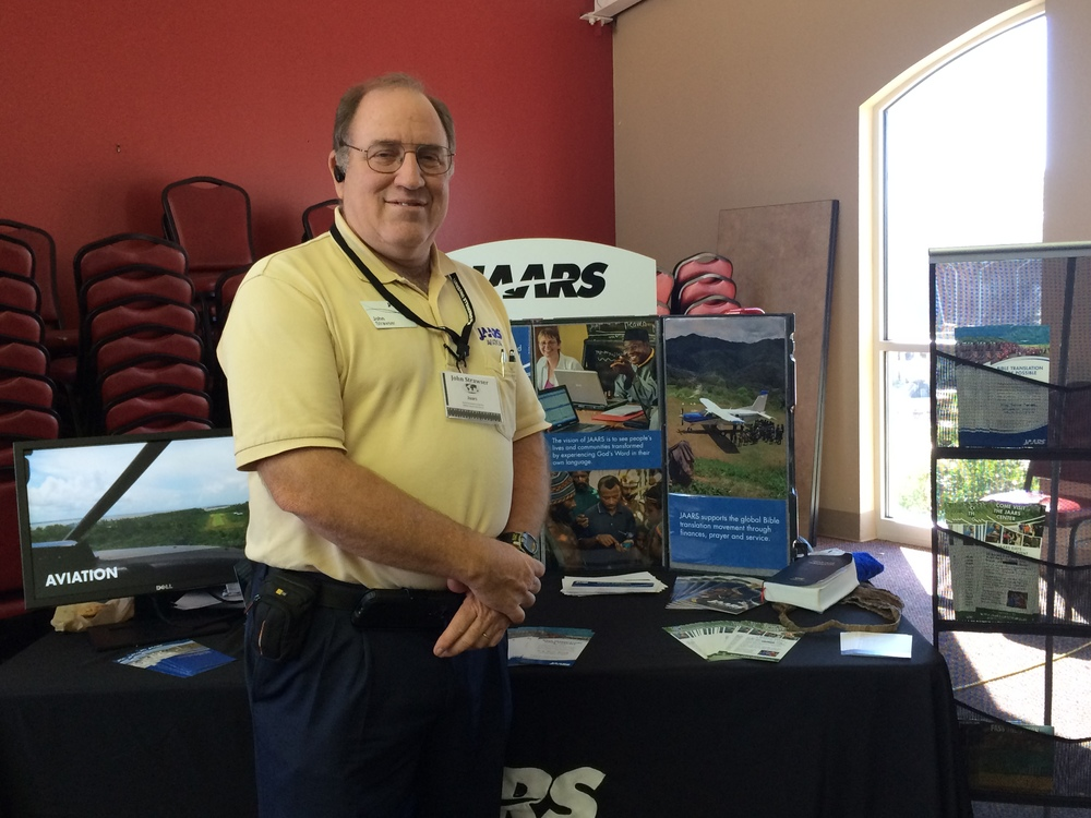 John Strawers takes time for a picture in front of his JAARS booth.