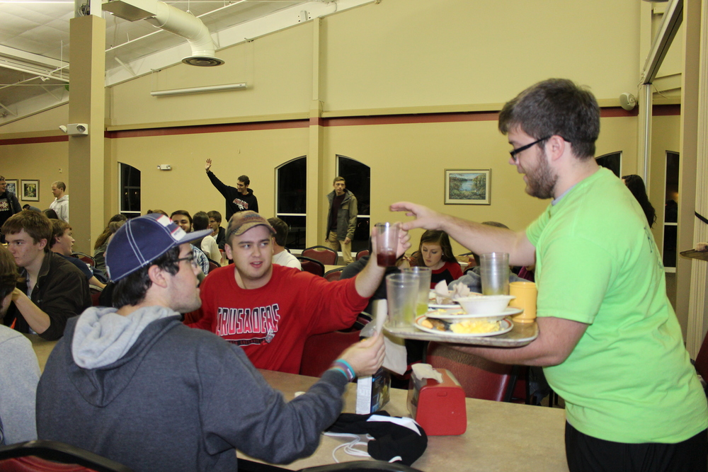 Jeremy Schultz, a Resident Assistant, takes students' dirty dishes during the late night breakfast on Thursday.