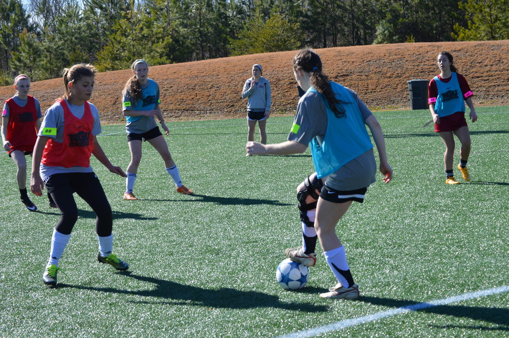 The main goal for the student with the ball was to find a way to score for her team.