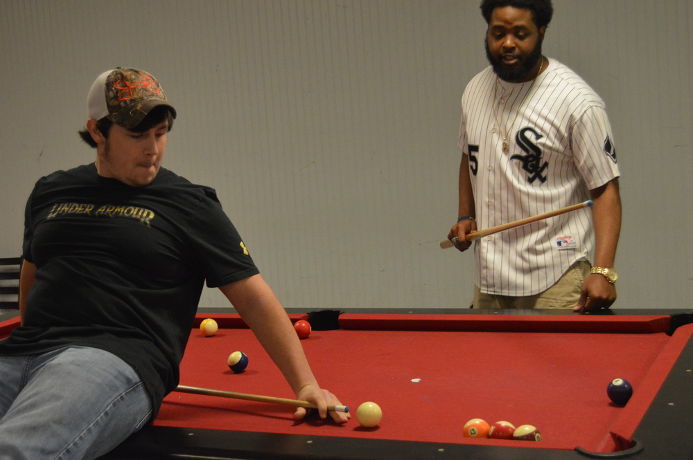 CJ Neal watches as Strib Crump performs a combination trick shot.