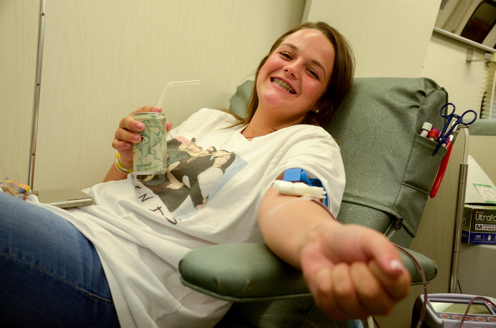 Freshma, Jennifer Garrett sips on her soda while giving blood to ensure that everything goes smoothly. Garrett has given blood twice and says she does it because it is for a good cause.
