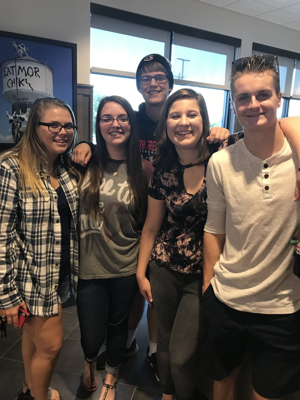 Meredith Kimmer (freshman), Danielle Sumner (freshman), Avery McGrail (freshman), Naomi Schaaf (freshman) and Matt Stromlund (freshman) enjoy hanging out with eachother at the Chick-fil-A grand opening.