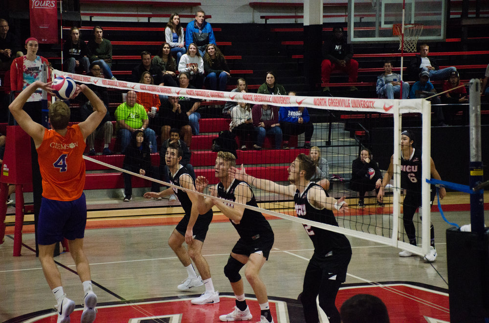 Grayson Lawrence (junior), Ben Hamsho (sophomore) and Aaron Campbell (junior) get ready to block a spike from Clemson.