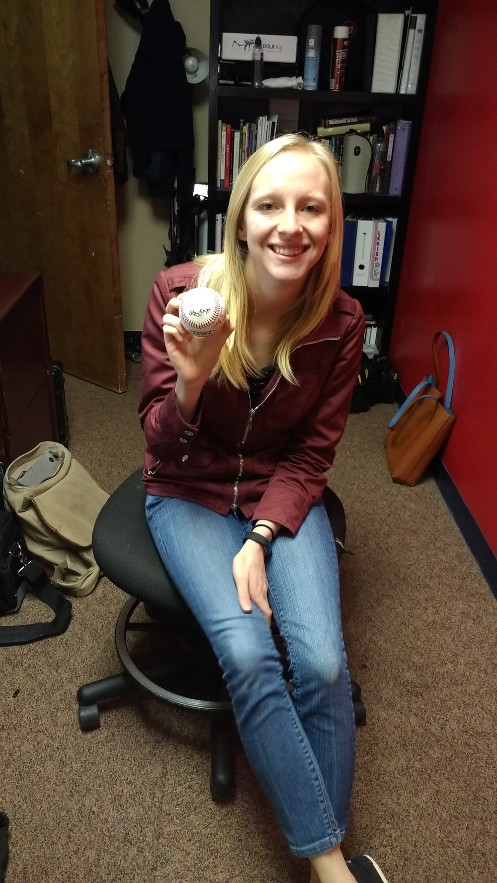 Mary Erny ('16 - Broadcast Media) holding her favorite gift. A baseball signed by all of her family members.
