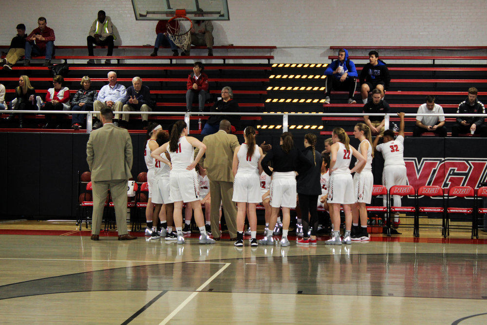 The NGU Women's Basketball team huddles together during a time out to listen to their coach.