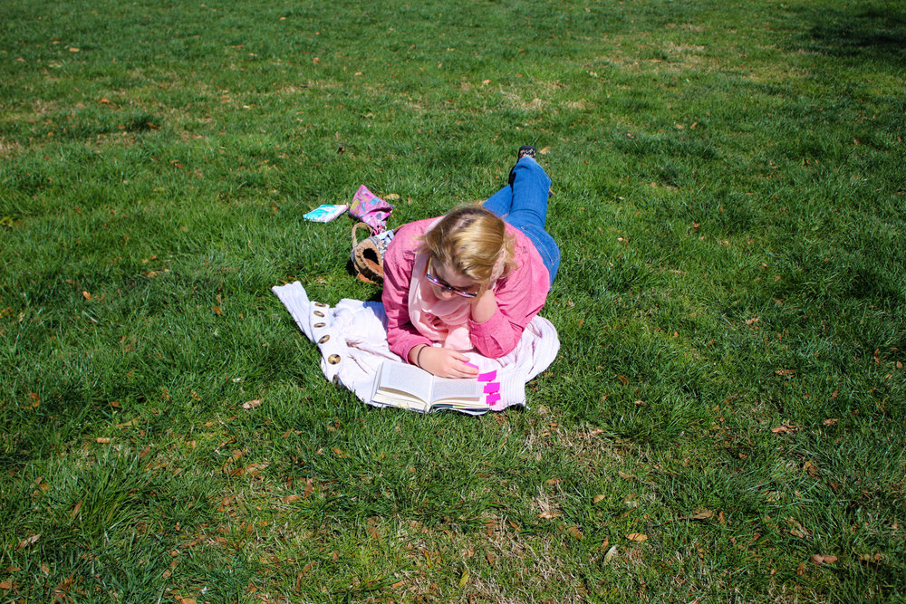 Linnea Stevens,a studio art major, enjoys the pleasant weather as she lays on the grass while reading.