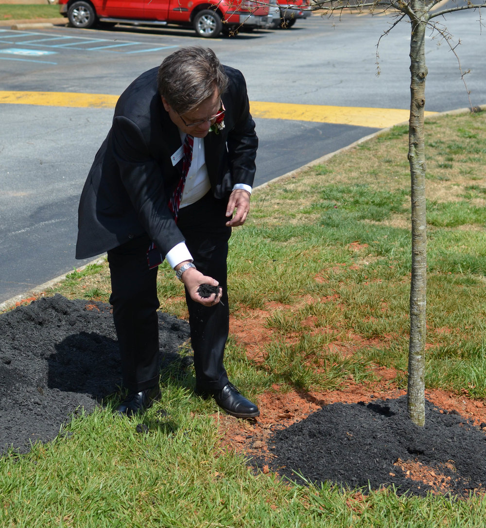 North Greenville President Dr. Gene Fant pouring dirt in traditional fashion.