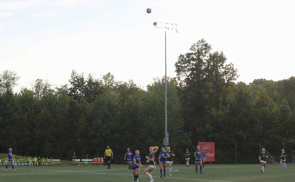 NGU and Lander university chasing after a ball after it had been juggled in the air by many diferent players on opposing teams.