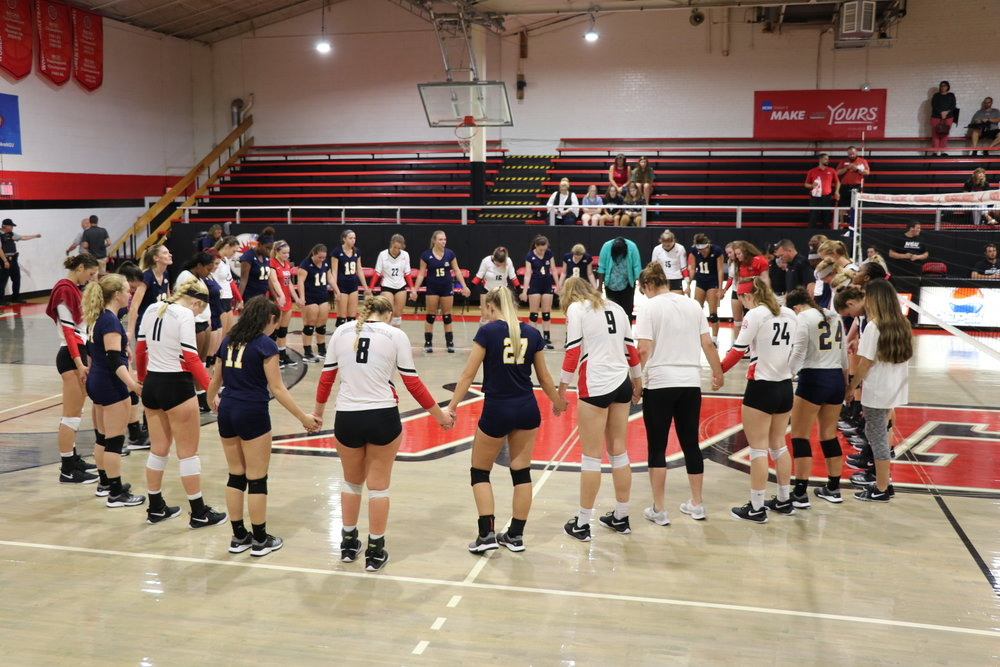 The two teams join hands and pray together after the game.