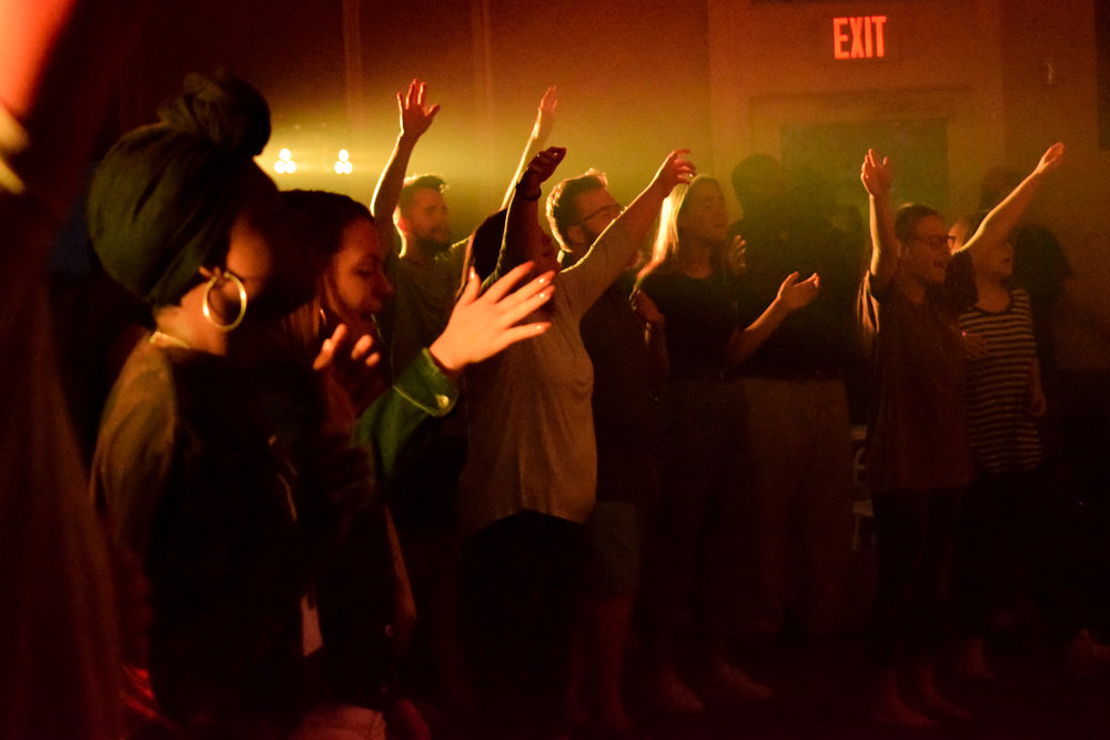 The audience feels the Spirit move as they sing along with the band and raise their hands in worship.