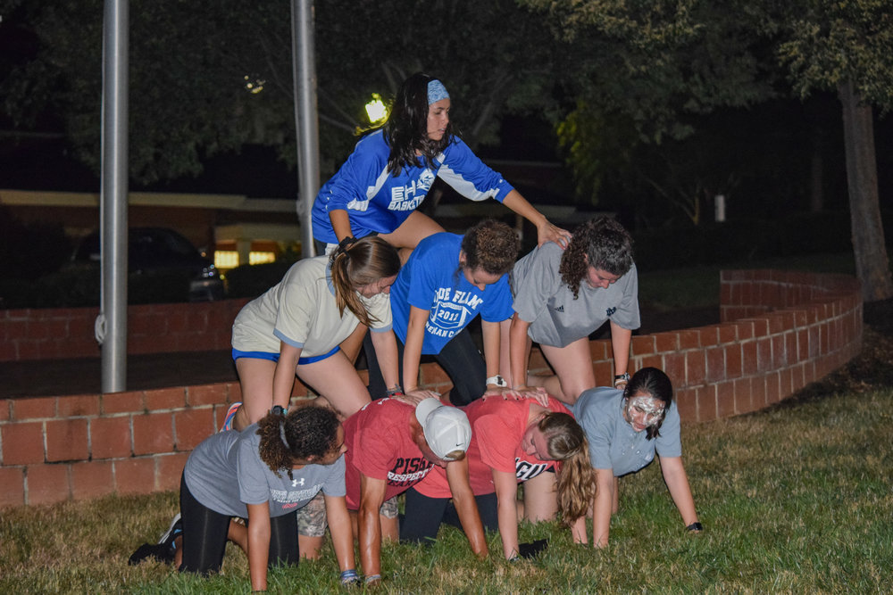 The health science club builds upon each other to form a pyramid before they can ring the bell to stop their time.