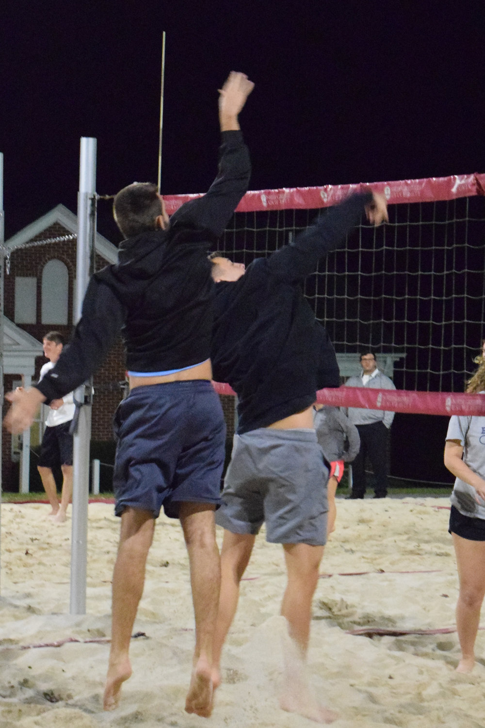 Junior, Landon Murray, jumps up behind junior, John Mark Trainer to help make sure the ball gets over the net.