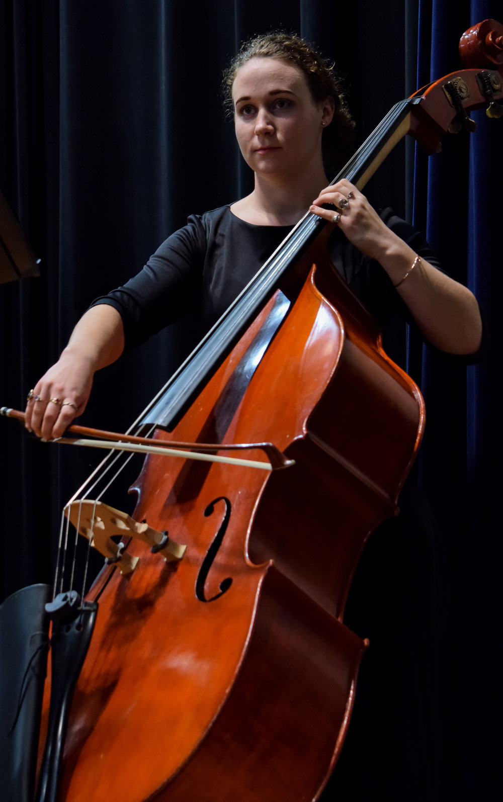 Senior, Francesca Scott looks off to the distance as she practices her double bass before the concert.