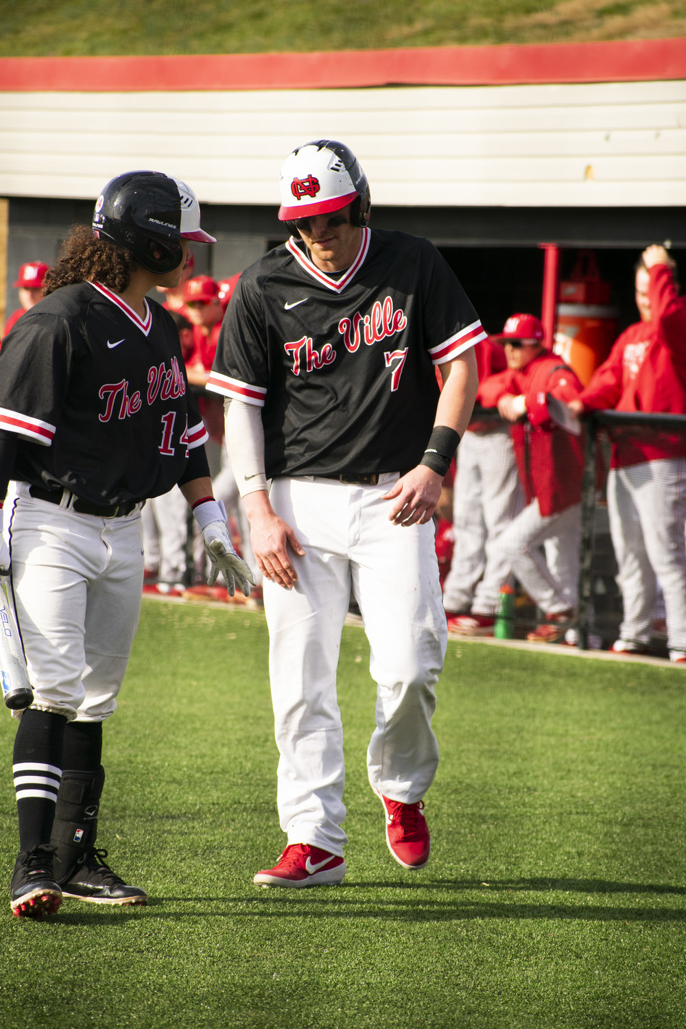 Sophomore Elvin Rosa (14) congratulates Junior Michael Neustifter (7) for just finishing running the bases, scoring points for the team.