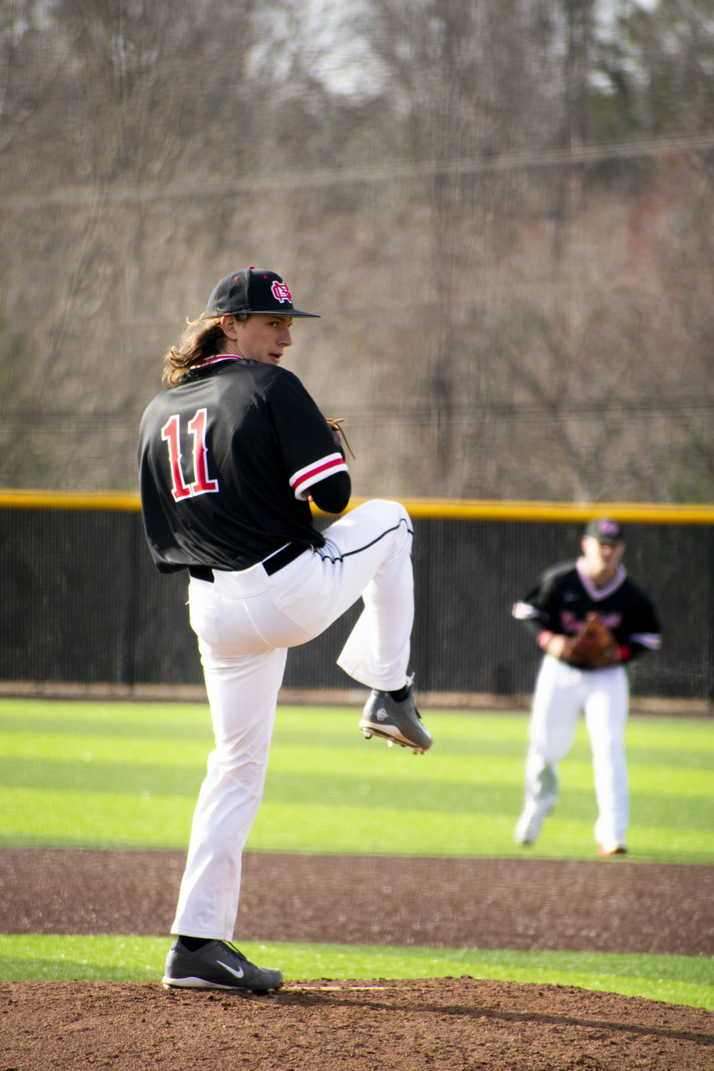 Junior Michael Giacone (11) pitches the ball.
