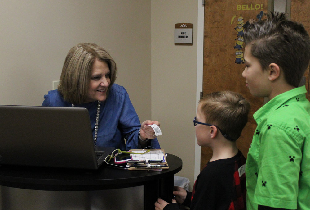 On Sunday mornings, children from ages one to 12 are electronically checked in specifically into their class according to age. Here, LeeAnn Streetman, the children's pastor's wife, welcomes our youth Jaxson McManus and Brian Fowler.