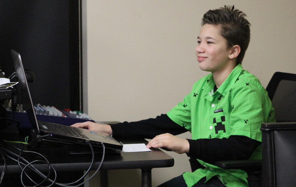 Fifth grader, Brian Fowler serves as the technician and computer operator for Trinity Kids.