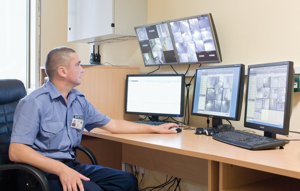security personnel monitoring security cameras