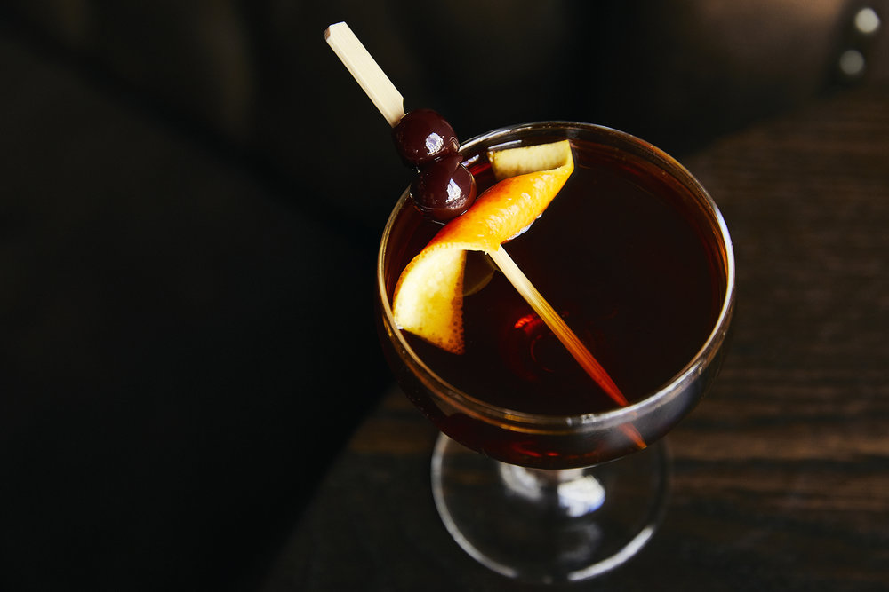 kimpton-seattle-washington-bookstore-bar-cafe-cocktail-whiskey-cherries-orange-garnish.jpg
