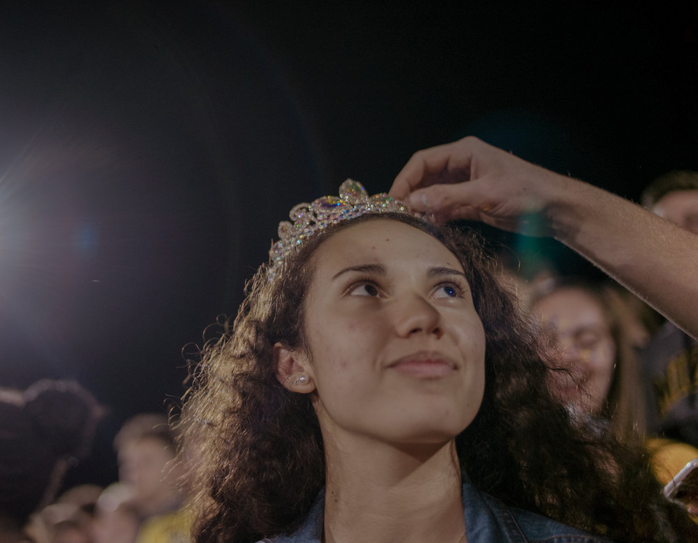"""Battle High School senior Joseph Lee fixes senior Sarah Higgins' homecoming-queen crown. """"I'm just happy to raise money for charity,"""" Higgins raised $1,678 for charity."""