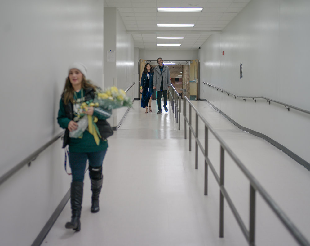 Student council adviser Kelley Wittenborn carries a bouquet of flowers for the currently undisclosed homecoming queen as Moy Zhong and her boyfriend Kai Ford walk down the hall towards the south exit of Rock Bridge High School on Oct. 12. Wittenborn has been the student council adviser for over four years.
