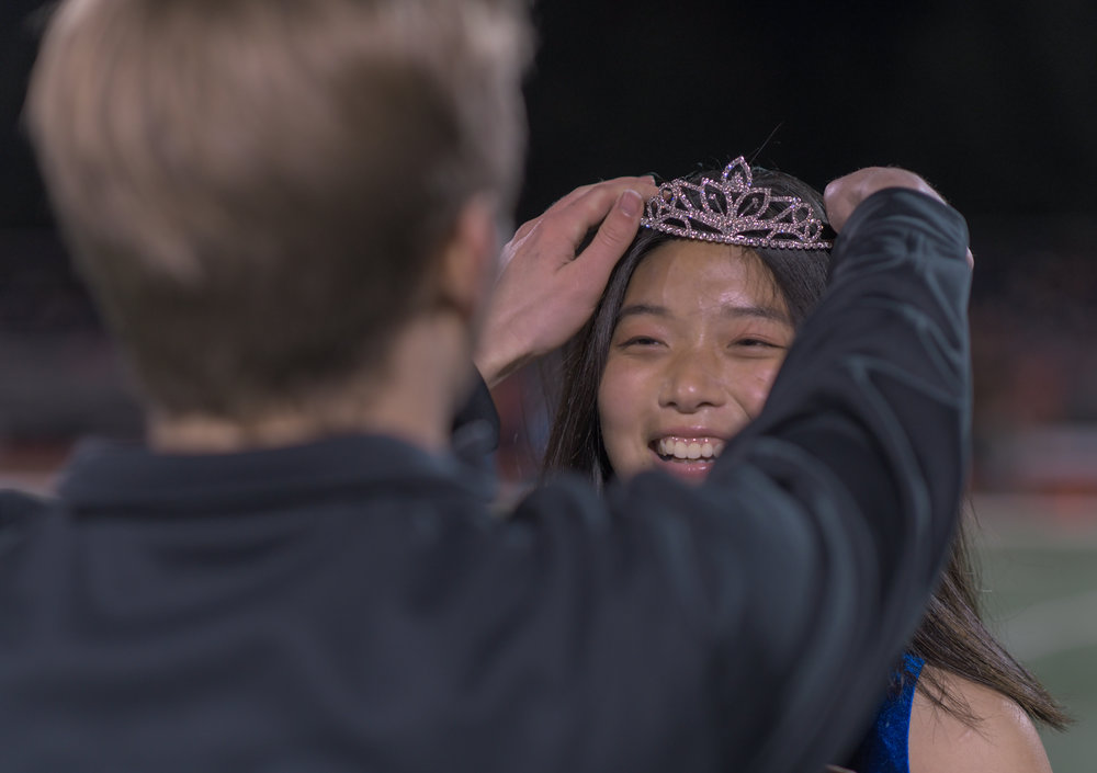 """Previous homecoming royalty Ethan Hayes crowns Moy Zhong Rock Bridge High School's 2018 homecoming queen on Oct. 12. Band members cheered """"go Moy,"""" from the endzone of the field."""
