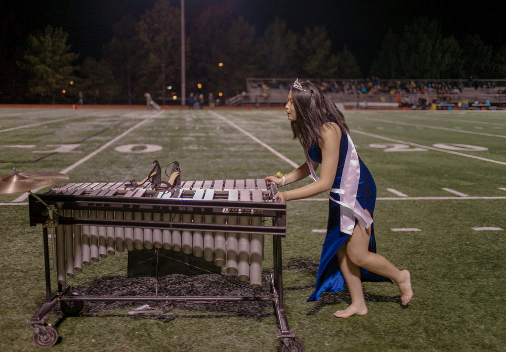 """Moy Zhong pushes her xylophone off of the Rock Bridge High School football field at a game against Helias Catholic High School on Oct. 12 at Rock Bridge. The regiment enacted scenes to Michael Jackson's 1982 """"Thriller"""" in the Emerald Regiment's performance of """"When The Clock Strikes 12."""""""