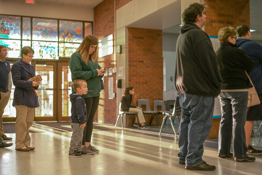 Columbia Resident Samantha Dempsey and her son Colton Dempsey, 3, wait in line to vote on Tuesday, Nov. 6, 2018 at John B. Lang Middle School in Columbia. The sun rose at 6:52 a.m. and shone directly into the polling location.
