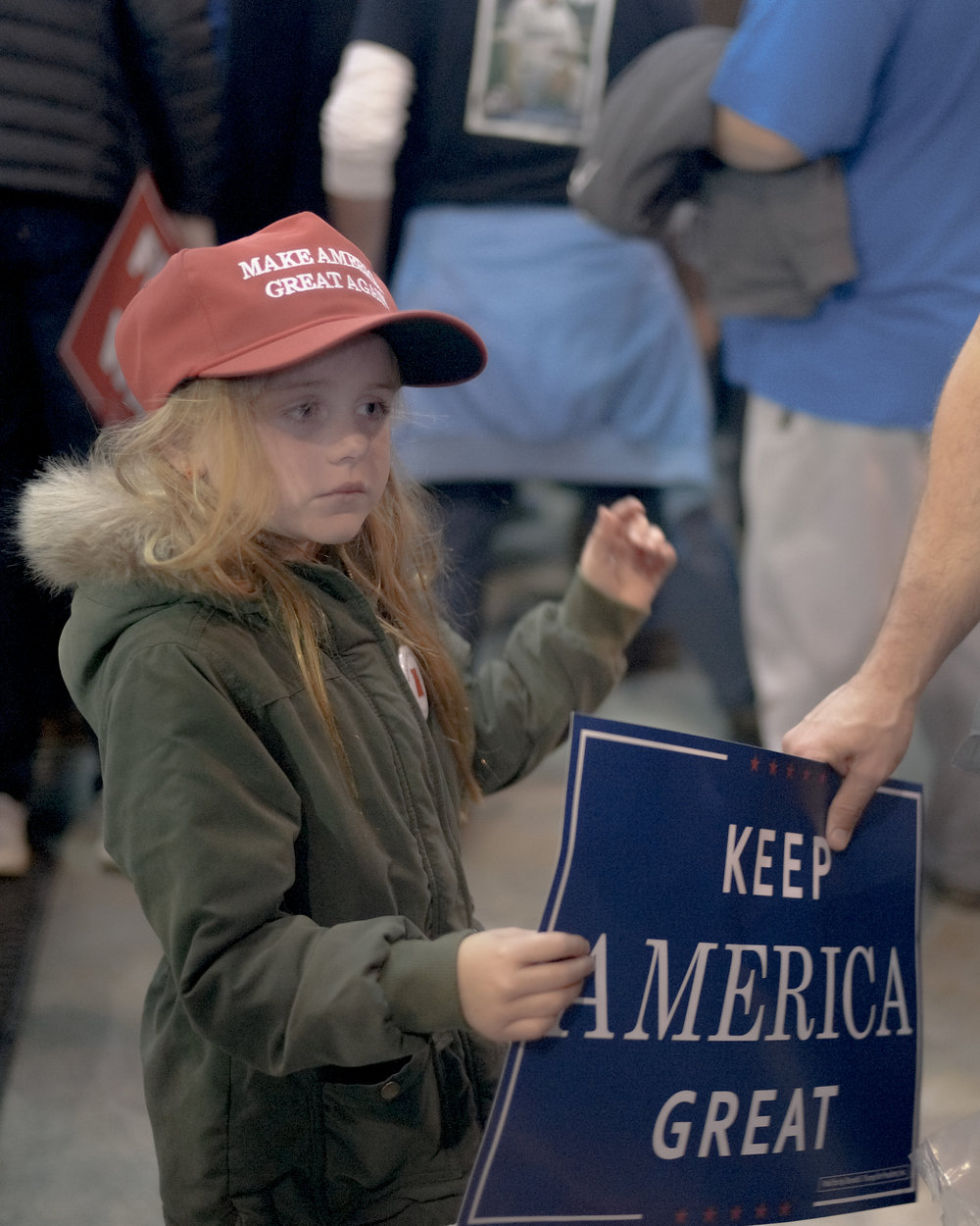 "A young girl is handed a sign at a Trump Rally in Columbia, Missouri on Thursday, November 2, 2018 at Columbia Regional Airport.   Thousands, including both supporters and protesters, traveled to the airport for the event which began just after 7 p.m., but some attendees camped out the previous day. Arriving just before 7 p.m. via Air Force One, the president spoke of himself and about current topics such as birthright, Brett Kavanaugh, Claire McCaskill, and Josh Hawley. Trump-centric memorabilia including hats, shirts and signs were sold and spread throughout the crowd, as well as the more localized ""Tigers for Trump"" signs. Two protests were held in response to the president's visit."