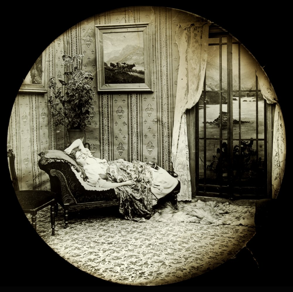 This woman feels faint even just thinking about all the stuff she has to get done by Christmas and has had to retire to her divan. [Lady sleeping on couch], ca. 1900. Glass lantern slide, State Library of Victoria, accession number H33823/39.