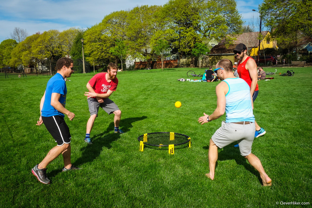 4 guys in a park playing Spikeball