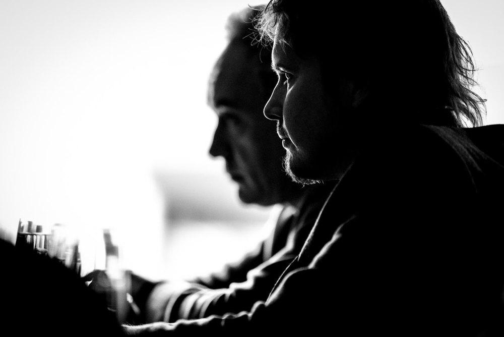 Pensive chefs Grant Achatz and Ferran Adria being interviewed by a journalist (Balena, Chicago, IL).