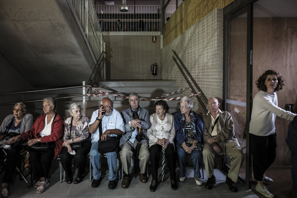 "aged people waiting to vote at the entrance of ""Escola L'Univers"" in Gracia District"