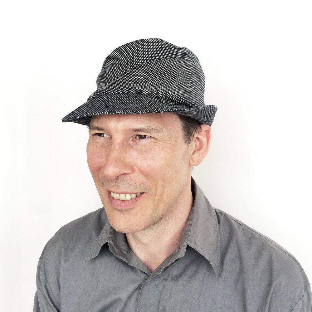 Adrian wears 'Sedley' trilby hat in navy/white cotton   buy online