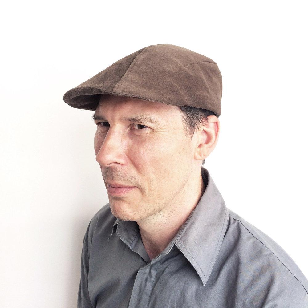 Adrian wears 'Garvey' flat cap in suede   buy online