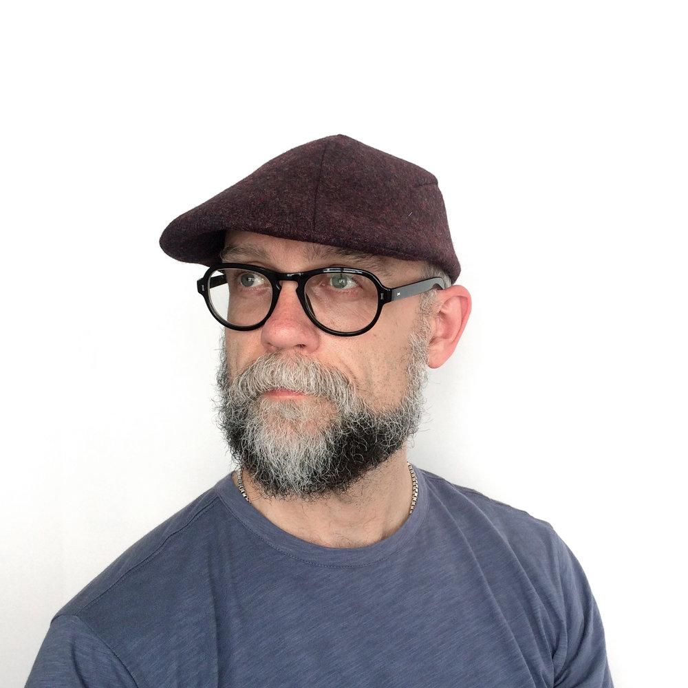 James wears 'Garvey' flat cap in burgundy wool tweed   buy online