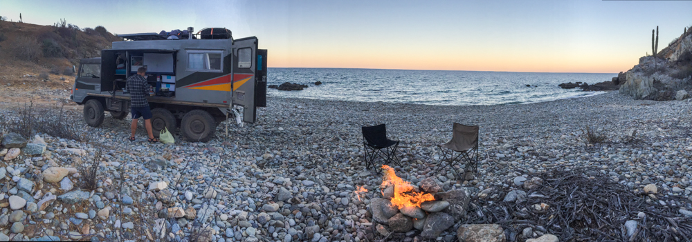 The rocky cove with dinner on the fire.