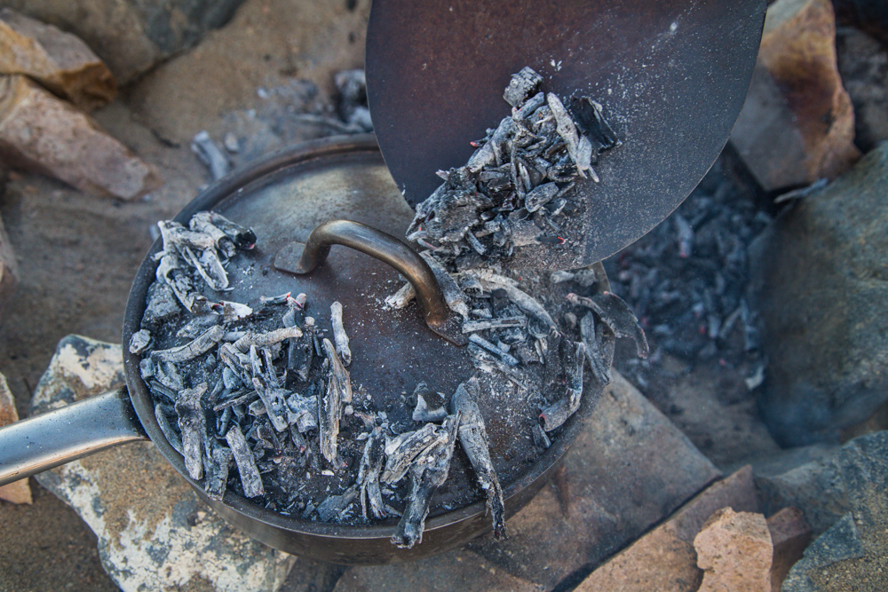 Piling coals on top of the dutch oven pan.