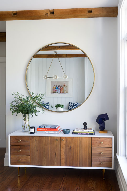 The mirror above this custom walnut sideboard reflects the  Apparatus Studio Trapeze  light fixture, featured in the breakfast nook. Above the sunroom (photo, left) hang three  Moooi Random  pendant lights. Varying sizes and staggering heights compliment the linearity of the exposed beam ceiling.