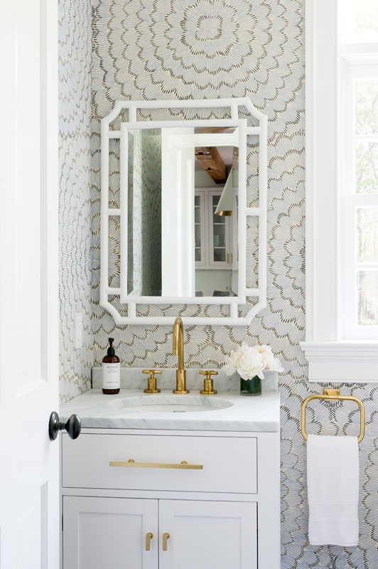 The powder room features antique brass accents and  Celerie Kemble  wallpaper that speak to both the youthfully modern and classically  Hamptons  styles that this home embodies.