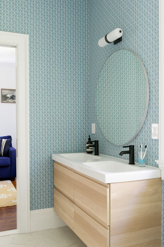 The children's  Jack-and-Jill  bathroom features geometric  Serena and Lily  wallpaper that turns a shared space into a charismatic extension of the connected bedrooms.