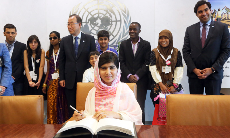 Malala Yousafzai signs United Nations Secretary-General Ban Ki-moon's guest books at United Nations headquarters. Photo courtesy of the Associated Press.