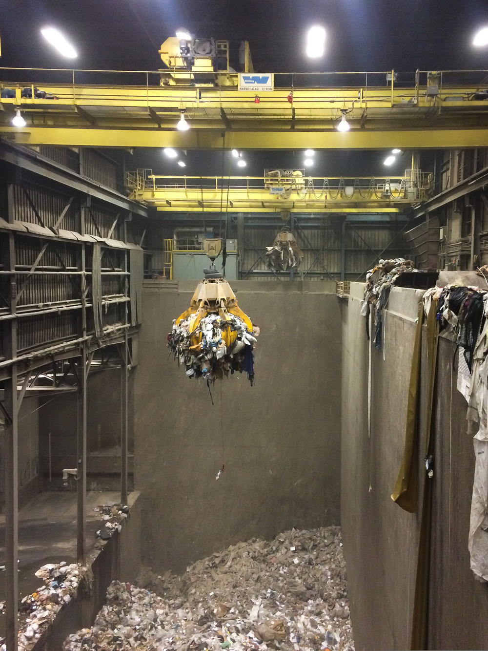 The tipping floor on the left is where garbage trucks dump their loads. Waste is then pushed into the pit. The crane moves waste around - pulling out large objects like mattresses and bicycles. Loads are then craned into the burners on the right, where waste is incinerated, and heat captured and turned into energy.