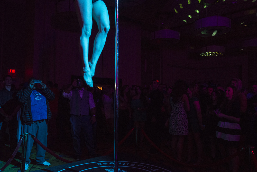 A man takes a photo of the Pole Fitness performer at the Party with the Pros event, the Official After-Party of the Arnold Classic, at the Hollywood Casino in Columbus, Ohio on Saturday, Mar. 8, 2015.