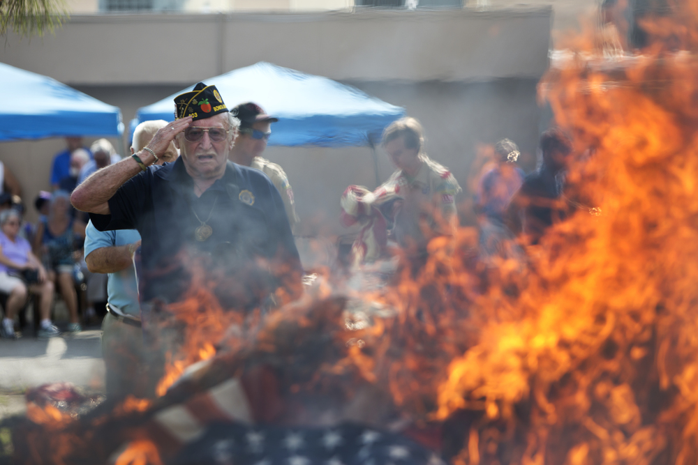 """Bernie Lurye, 83, of Bonita Springs, salutes at the American flags, which were burned as a part of the retirement ceremony of unserviceable American flags at the American Legion Post 303 on Tuesday, June 14, 2016 in Bonita Springs, Florida. When the United States flag becomes worn, torn, faded or badly soiled, it is """"retired"""", traditionally through incineration. The ceremony has been an integral part of American Legion ritual since 1937."""