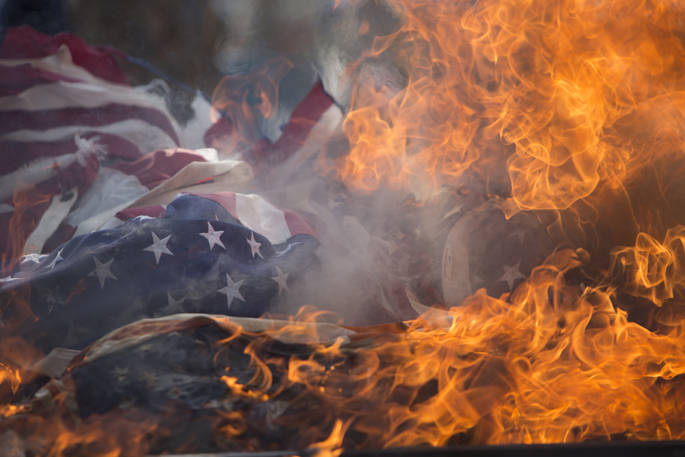 Unserviceable American flags burn as a part of the retirement ceremony at the American Legion Post 303 on Tuesday, June 14, 2016 in Bonita Springs, Florida. Adam Prentiki III, Commander of the American Legion Post 303, says people donate unserviceable flags throughout the year and estimates they had about 1,500 flags for the ceremony.
