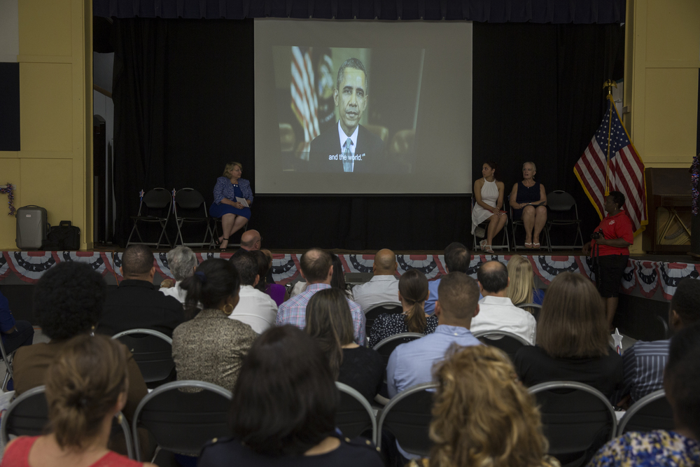 The newly sworn in American citizens listen to a congratulatory message from President Barack Obama on World Refugee Day at Golden Gate Community Center on June 25, 2016 in Naples, Florida.