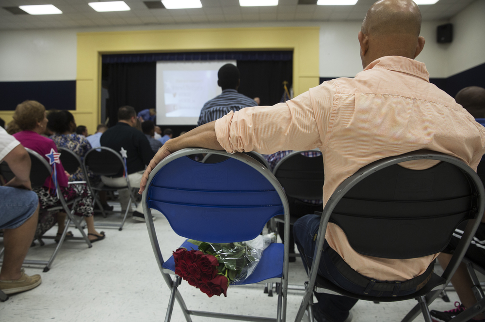 A man waits with roses during the Citizenship Ceremony on World Refugee Day at Golden Gate Community Center on June 25, 2016 in Naples, Florida.