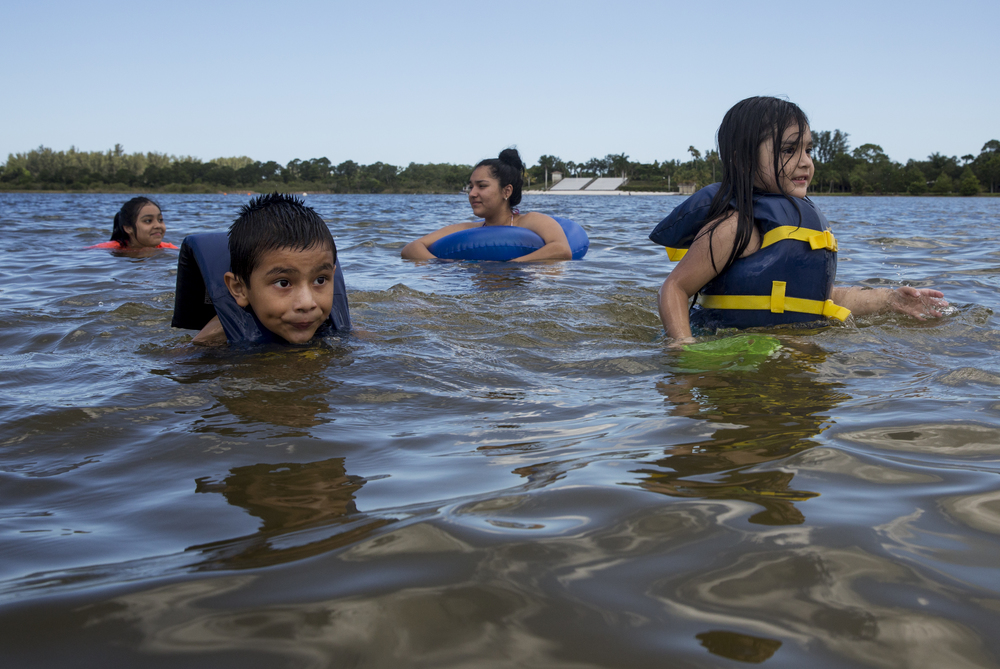 From left: Elizabeth Garcia, 11, Aries Ayala, 6, Paulina Garcia, 16, and Rosa Garcia, 4, all of Naples, swim together in Lake Avalon at Sugden Regional Park on June 23, 2016 in Naples, Florida.